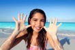 llatin teen girl playing beach smiling sandy hands