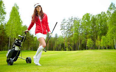 female golf player walking on fairway with their golf trolleys