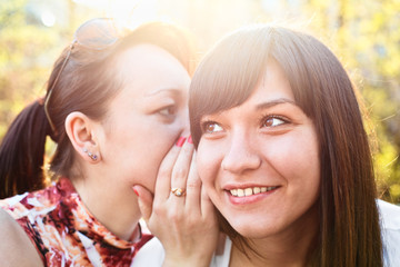 Young woman whispers something to girlfriend in her ear