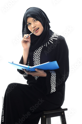 Beautiful muslim women bit a pen while thinking