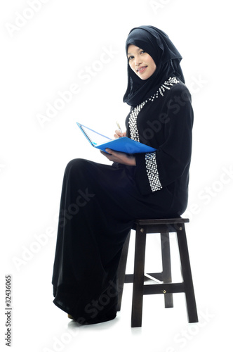 Beautiful muslim women smile while reading