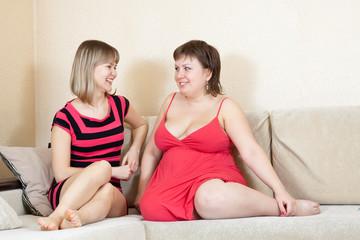 women talking on sofa in home