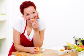hübsche rothaarige frau isst eine mandarine