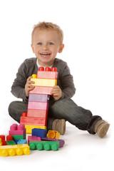 enfant jouant avec blocs plastiques