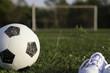 Постер, плакат: Футбольный мяч и детские белые кеды на футбольном поле