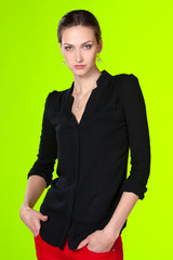 Young business female standing with her arms in the pockets
