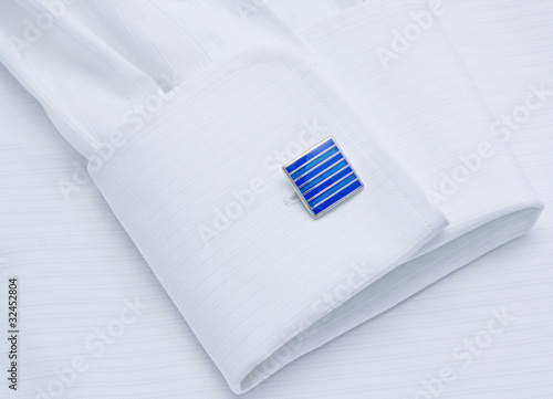 Leinwandbild Motiv Sleeve of a white shirt with a dark blue cuff link close up