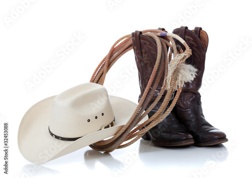Cowboy hat, boots and lariat on white - 32453088