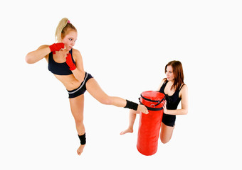 Attractive Caucasian fitness girls with a red boxing bag