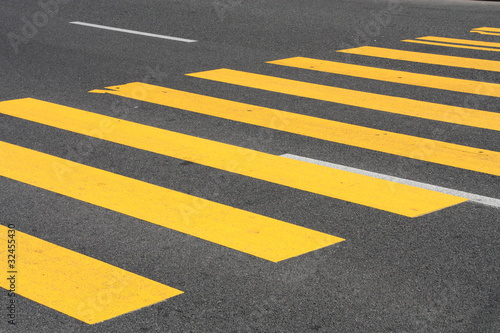 Yellow painted pedestrian crossing on the road.