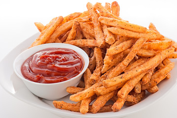 Plate of hot french fries and ketchup on a white plate