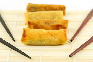 Chinese spring rolls with chopsticks on the bamboo mat