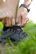 Trail runner tying shoe