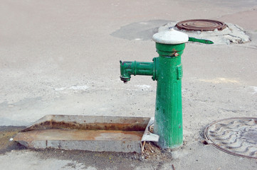 An old fashioned water pump above a rusty trough