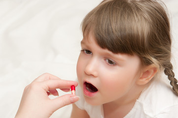 Woman give pill to little girl