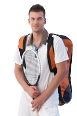 Young tennis player with equipments smiling