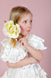 child in a white dress with a flower in hair
