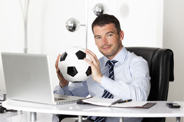 young businessman in office with computer and ball