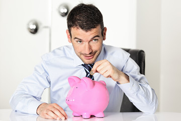 man with coin and pink piggy bank