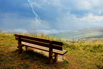 isolated bench in the natural park with storm incoming