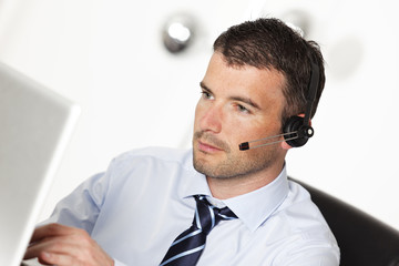 man working with headset and computer in office
