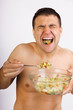 Young happy smiling man eating salad