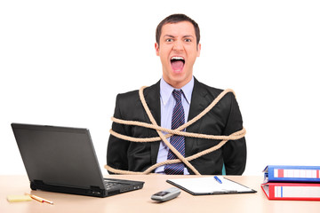 Businessman tied up with rope in the office