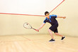 Squash player hiting a ball in a squash court