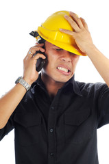 Workers wearing safety helmet tension while talk on mobile phone