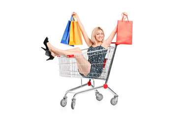 Happy woman with shopping bags posing in a shopping cart