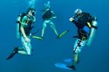 scuba divers descend on a dive site poster