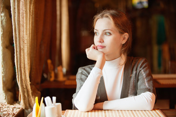 Young beautiful woman sits in cafe
