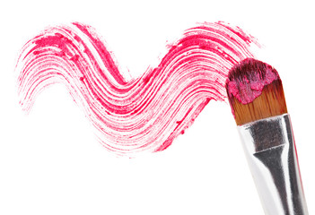 Pink lipstick stroke (sample) with makeup brush, isolated on whi