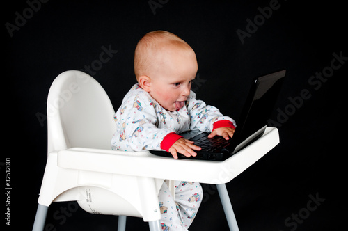 Baby with the laptop on the black backround