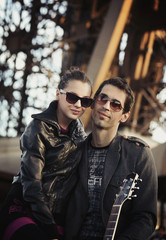 Handsome couple with sunglasses and guitar
