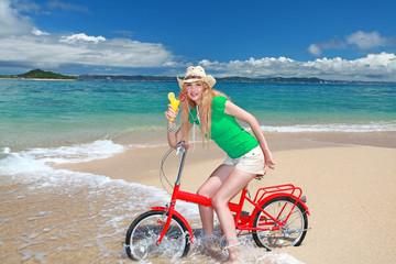 コマカ島のビーチで自転車に乗ってソフトドリンクを飲む笑顔の女性