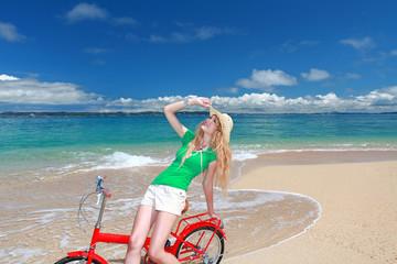 久高島のビーチで自転車に乗って大空を見上げる笑顔の女性