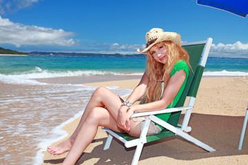 久高島の波打ち際でビーチチェアに座っている笑顔の女性