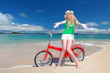 ビーチでサイクリングを楽しむ笑顔の女性