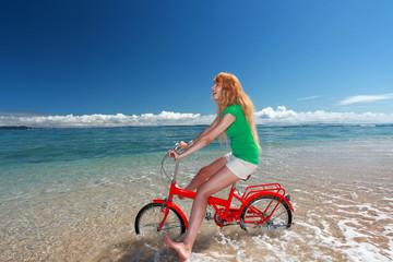 波打ち際を自転車で進む笑顔の女性
