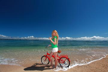 自転車で波打ち際まで来た笑顔の女性