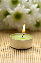 candle and daisy on bamboo stick straw mat
