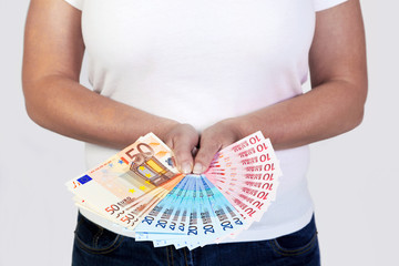 Hand holding a fan of Euro banknotes.