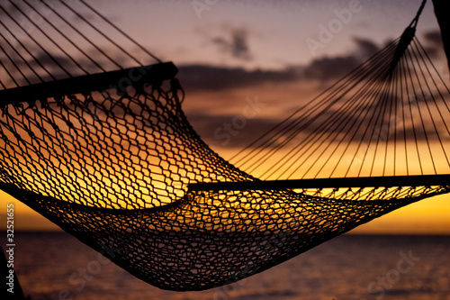 silouhette of hammock on beach overlooking ocean at sunset
