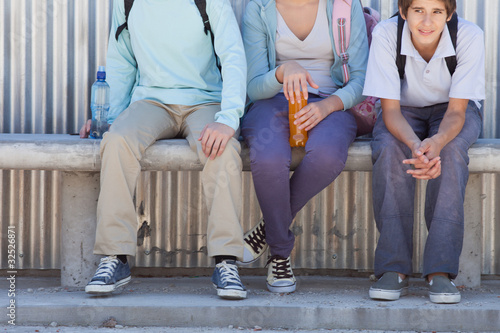 Three children sitting side by side on bench