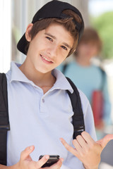 Boy with baseball cap and cell phone outdoors