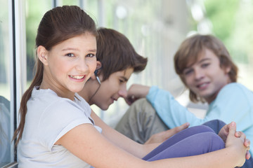 Smiling girl sitting outdoors with boys in the background