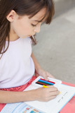 Girl drawing into schoolbook