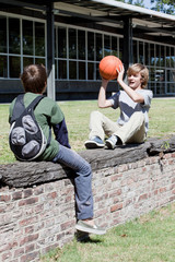 Two boys playing with basketball on stone wall