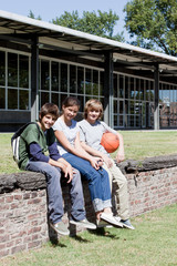 Three children sitting with basketball on stone wall